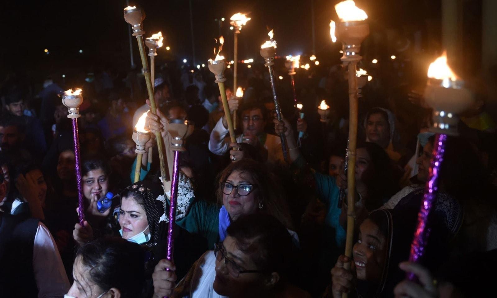 کراچی میں شہریوں نے شمع روشن کی ہوئی ہے — فوٹو: اے ایف پی