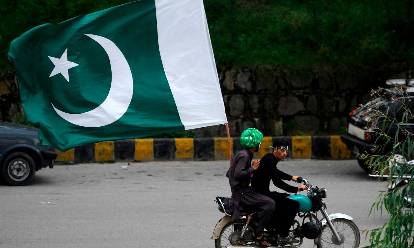 ملک بھر میں گاڑیوں اور موٹر سائیکلوں پر لوگ جھنڈے لہراتے ہوئے نکلے — فوٹو: اے ایف پی