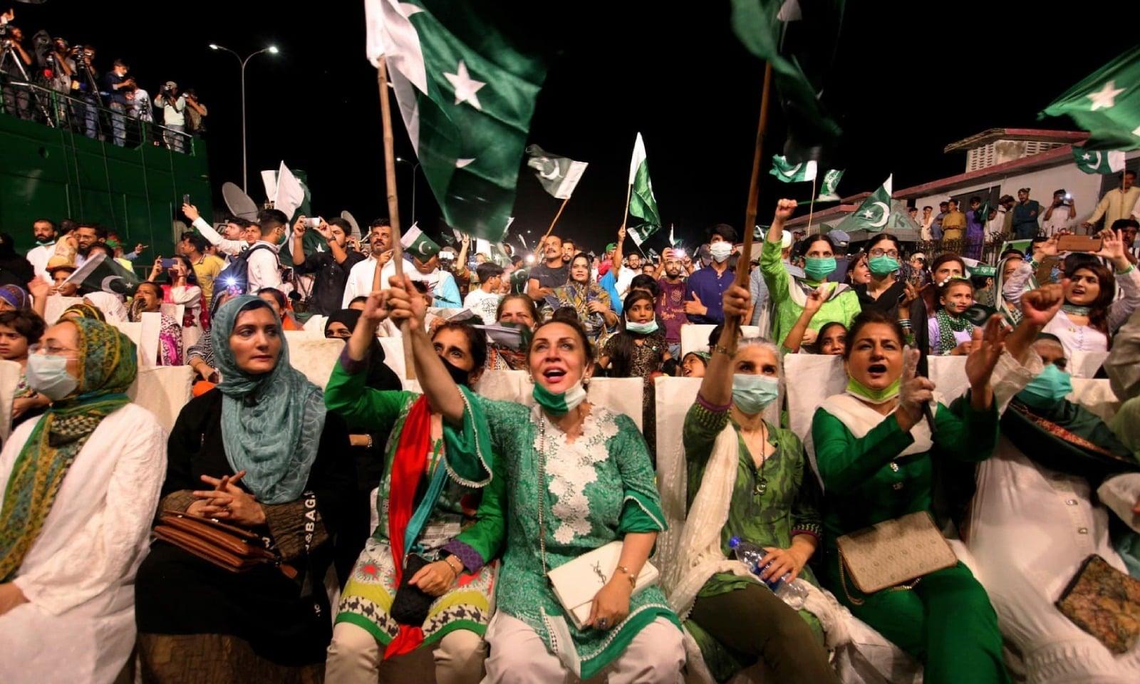کراچی میں آتش بازی دیکھتے ہوئے لوگ خوشی سے شور مچا رہے ہیں — فوٹو: اے پی