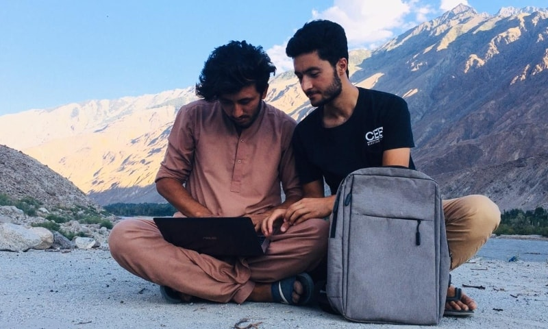 Mudasir Alam (R) and his friend work on a laptop sitting across a river in GB. — Photo by author
