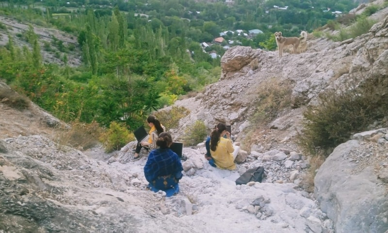 Karishma Nadir and her friends work on their laptops, sitting atop a hill hoping to catch internet signals, in Booni, Chitral. — Photo by author