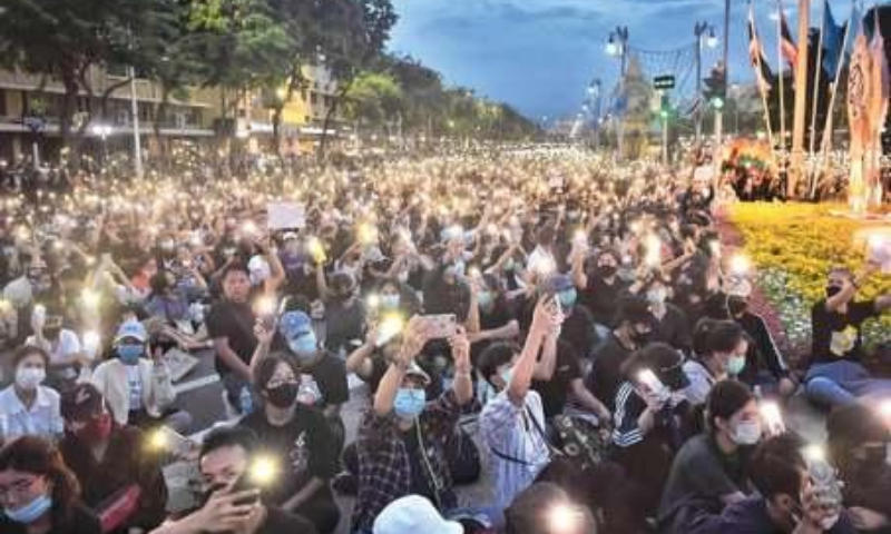 BANGKOK: Anti-government protesters hold up their phone flashlights during a rally at Democracy Monument on Sunday. — AFP