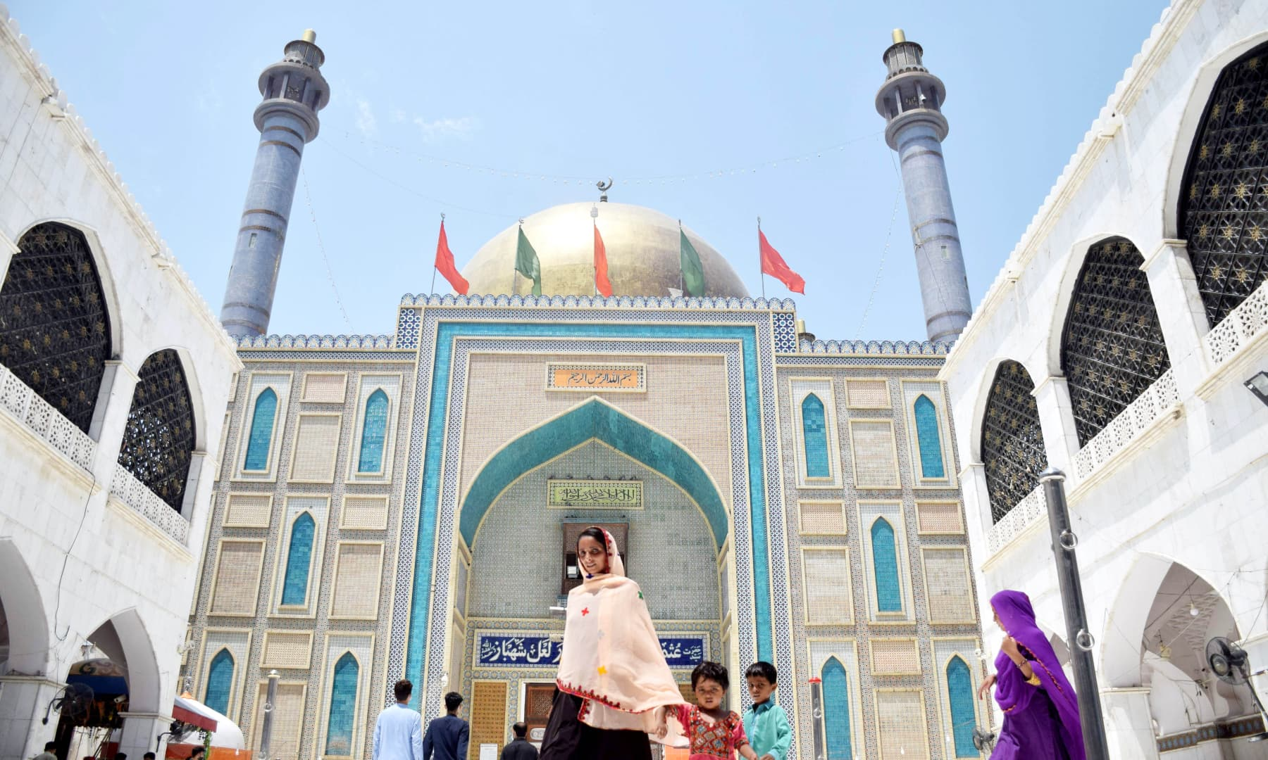 A woman comes out from Qadeemi Alam Pak's side entrance after paying her respects to Lal Shahbaz Qalandar.