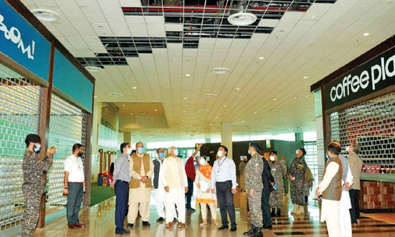 Aviation Minister Ghulam Sarwar Khan inspects the damage at Islamabad International Airport during his visit on Monday. — White Star