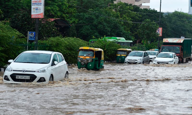 Commuters make their way along a waterlogged road following monsoon rainfalls in New Delhi on August 19, 2020. — AFP