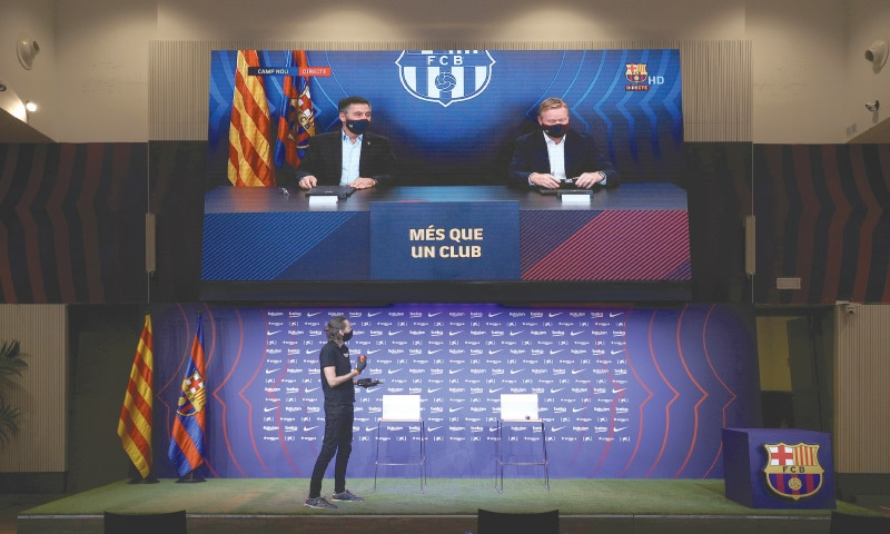 BARCELONA coach Ronald Koeman signs the contract as he is pictured on a big screen with president Josep Maria Bartomeu during the unveiling on Wednesday.--Reuters