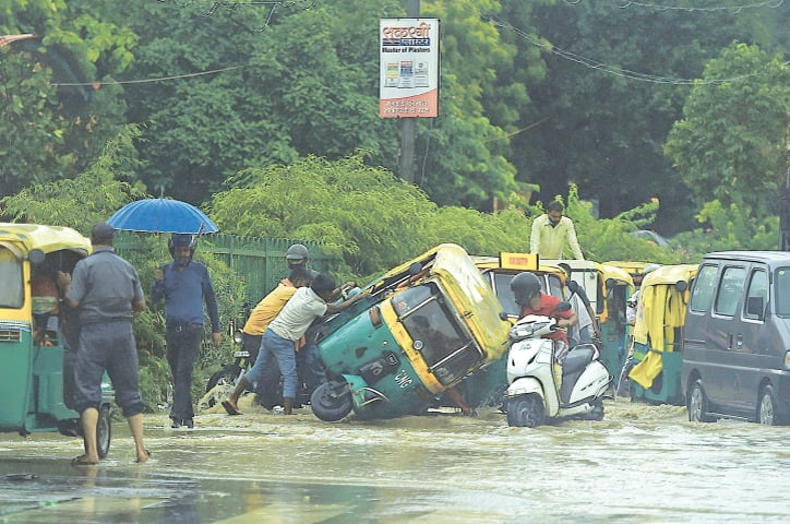 DELHI: People try to pull an overturned auto rickshaw on a flooded road after heavy rains here on Wednesday.—AFP
