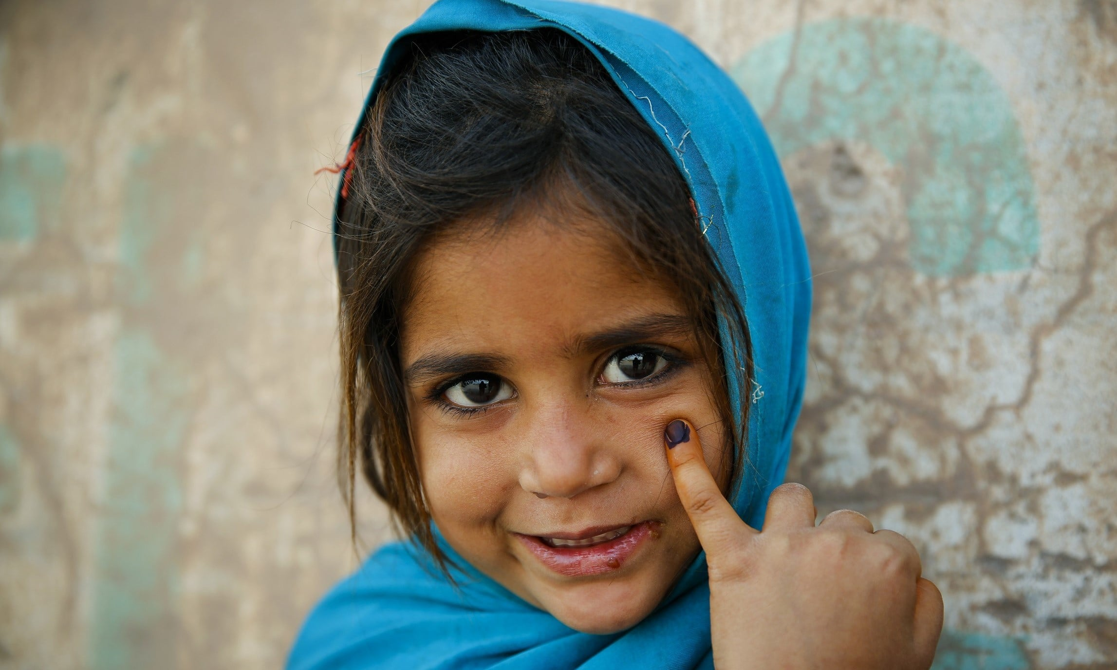 A child shows the her finger marked by ink after she was vaccinated against polio, in Peshawar. — Photo by Asad Zaidi/Courtesy: http://www.endpolio.com.pk