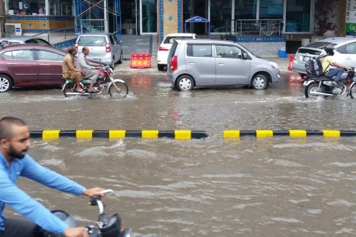 Commuters pass through an inundated road near Lahore's Defence Boulevard after heavy rainfall lashed the city through the night into Thursday morning. —  Dawn.com
