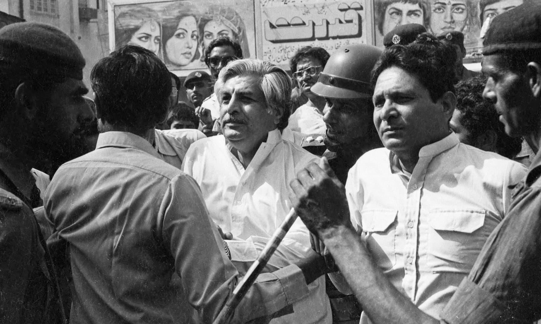 ایم آر ڈی لیڈران غلام مصطفیٰ جتوئی اور معراج محمد خان کو ضیا آمریت کے خاتمے اور جمہوریت کی بحالی کے لیے جاری احتجاجی مظاہرے کے دوران پولیس حراست میں لے رہی ہے — تصویر بشکریہ سینئر فوٹوجرنلسٹ زاہد حسین