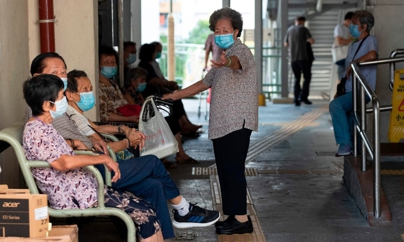 People wearing face masks as a precautionary measure against Covid-19 sit together in Hong Kong on August 23.  — AFP
