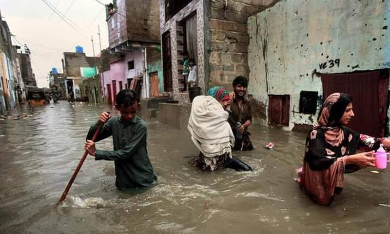 Residents wade through a flooded street in Karachi on Tuesday. — Photo: Twitter