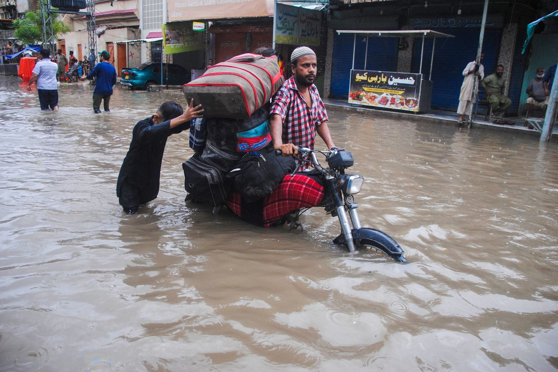 A man pushes a motorcycle transporting bags through a flooded street after heavy monsoon showers in Hyderabad on Tuesday, August 25. — AFP