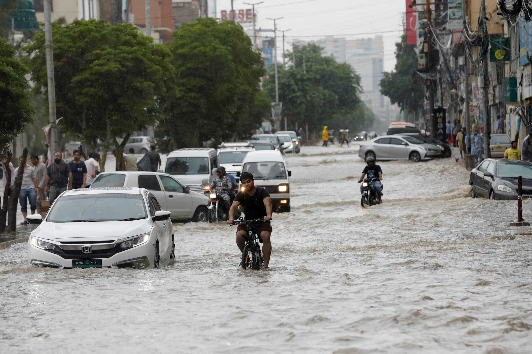 Commuters drive in a flooded street during the monsoon rain on Tuesday. — Reuters