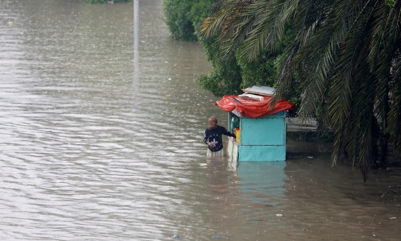 A man stands outside his cabin shop on a flooded street during the monsoon rain in Karachi on Tuesday. —  Reuters