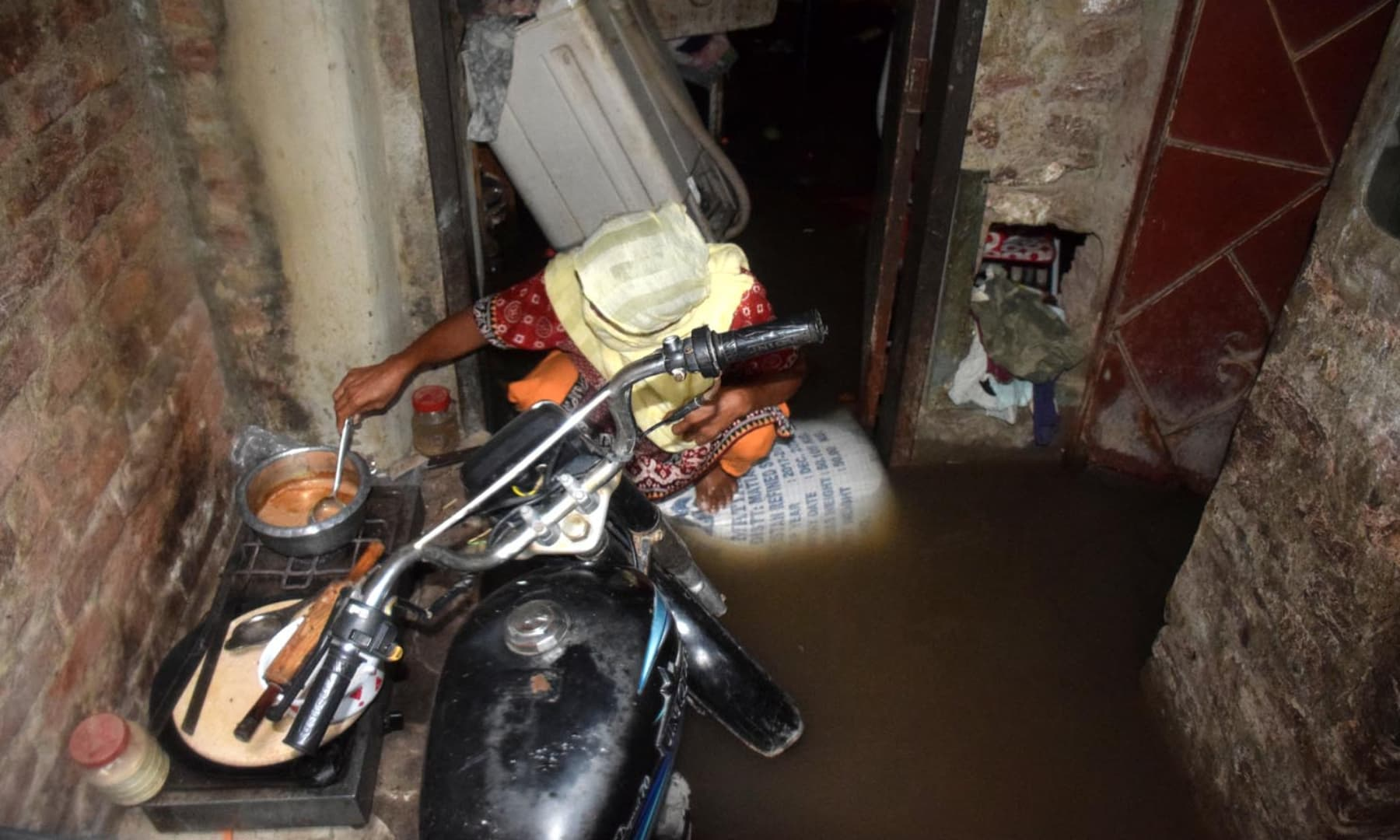 A woman prepares tea in a flooded house located in unit-2 Latifabad of Hyderabad. — Umair Ali