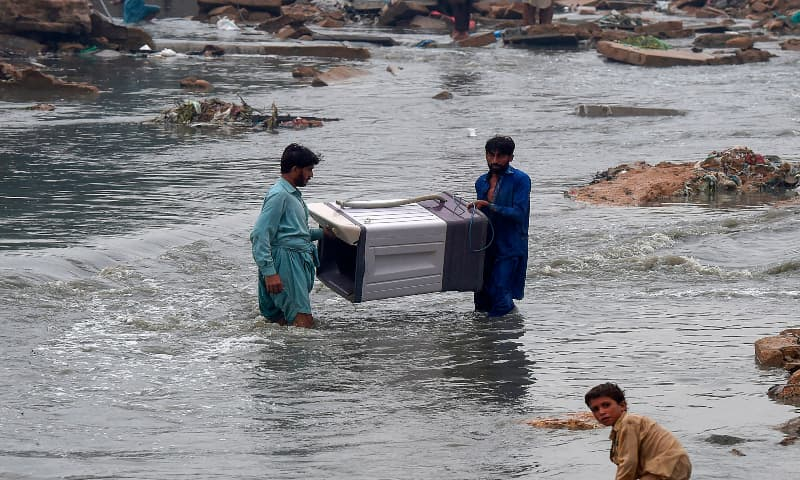 People carry a washing machine through a flooded residential area after heavy monsoon rains in Karachi on August 27, 2020. — AFP