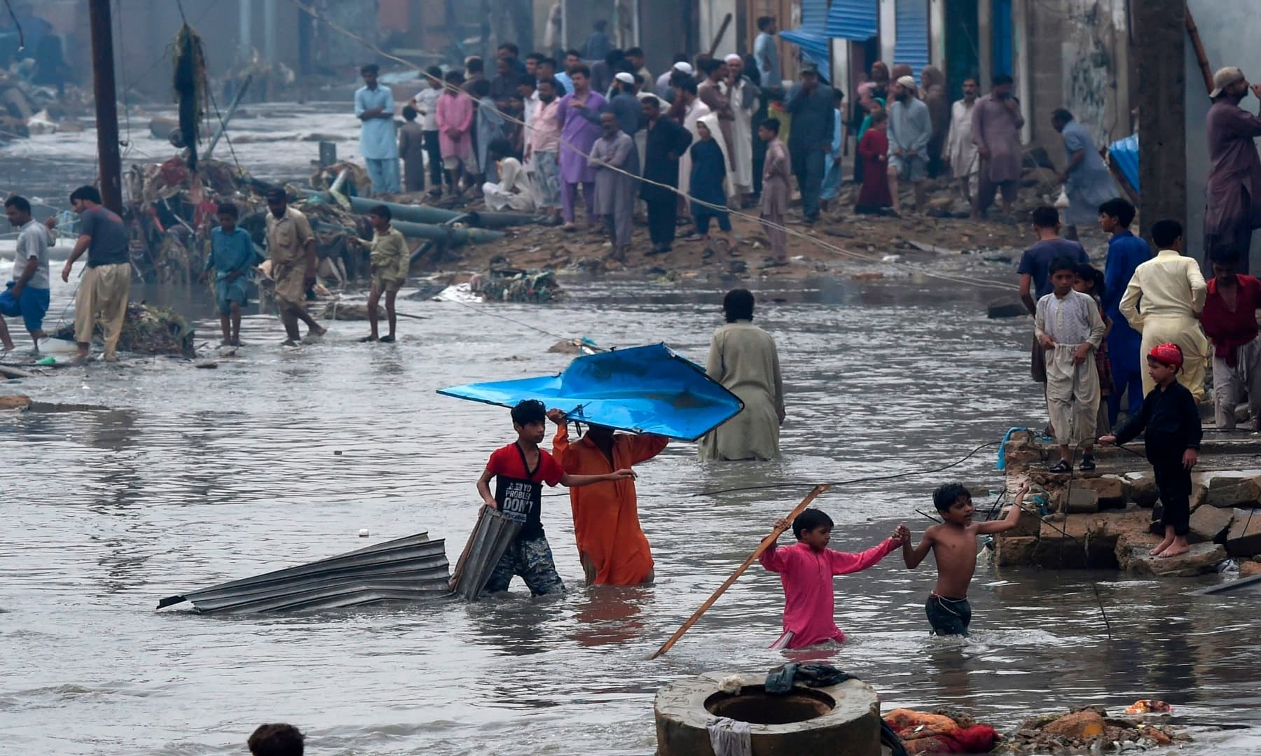 People wade through a flooded residential area after heavy monsoon rains in Karachi on August 27, 2020. — AFP