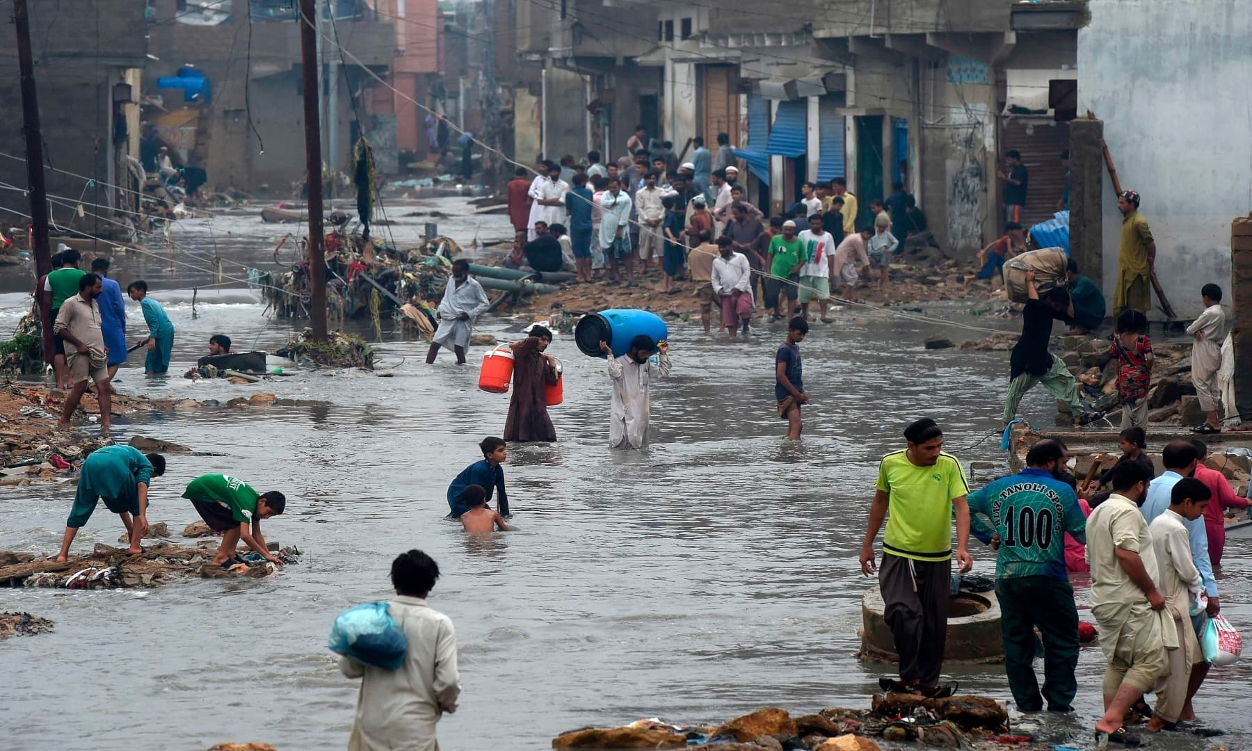 People wade through a flooded residential area after heavy monsoon rains. — AFP