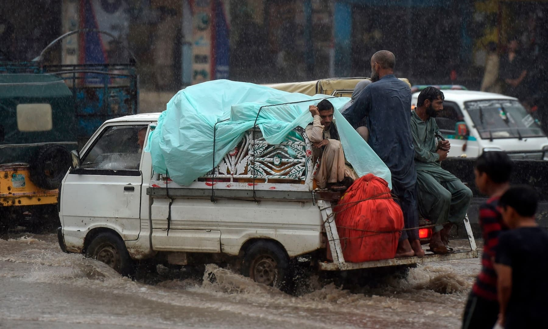 People ride in a vehicle during heavy monsoon rains in Karachi. — AFP