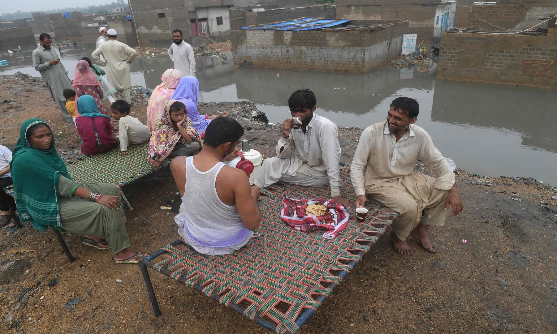 Flood-affected people gather on a higher place following heavy monsoon rains in Karachi. — AFP