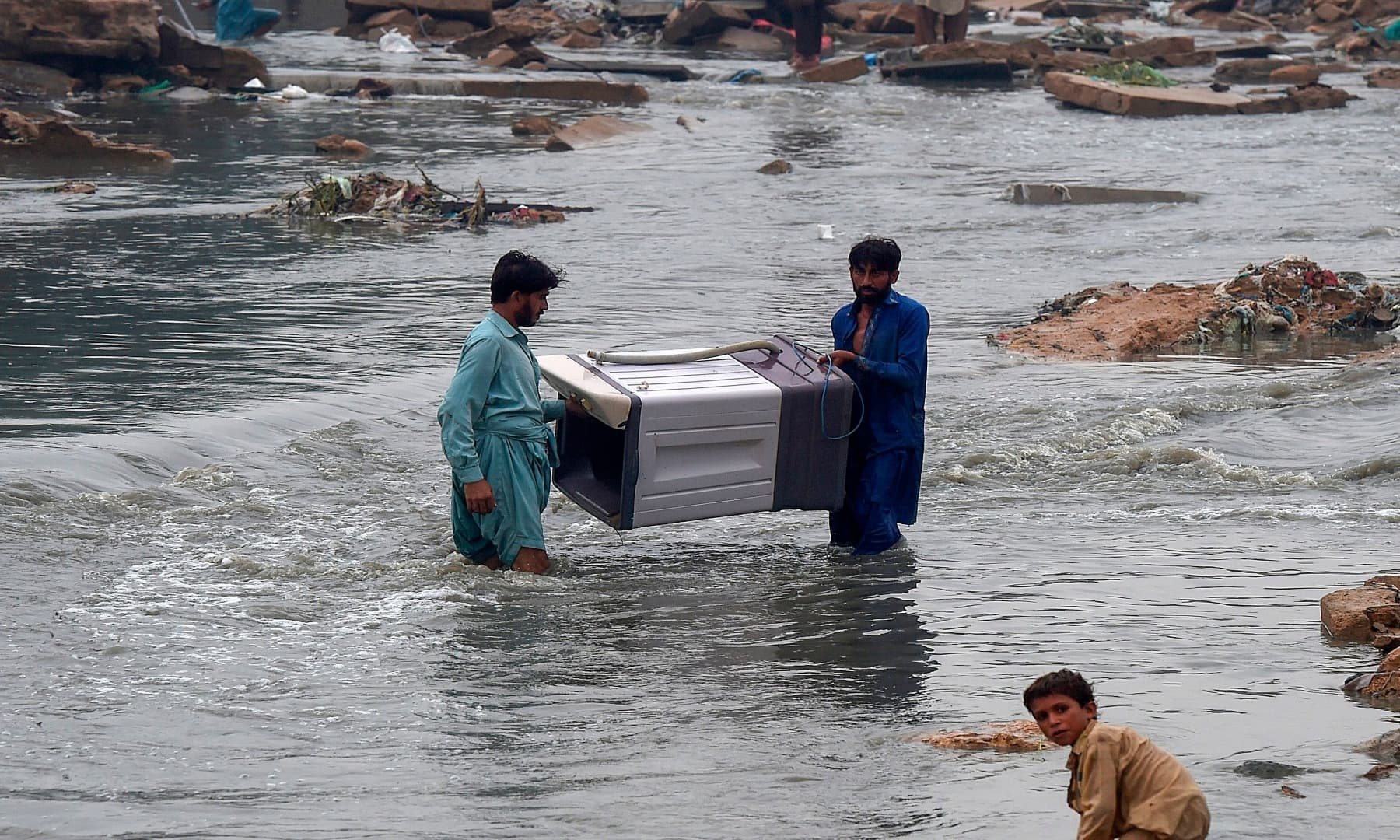 People carry a washing machine through a flooded residential area. — AFP