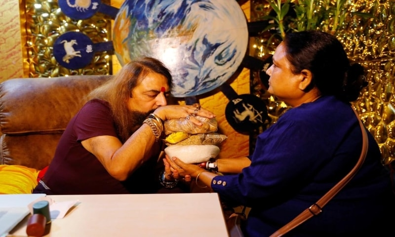 Sanjay Sharma, a mystic healer and astrologer, making prayers as her holds herbs in his hands before giving them to a client as Covid-19 spreads through India. — Reuters