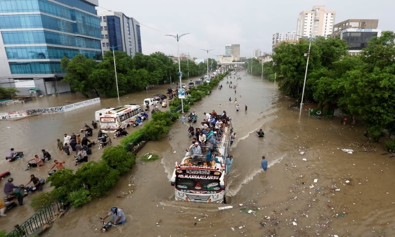 People sit atop a bus roof while others wade through a flooded road during monsoon rain in Karachi on August 27, 2020. — Reuters