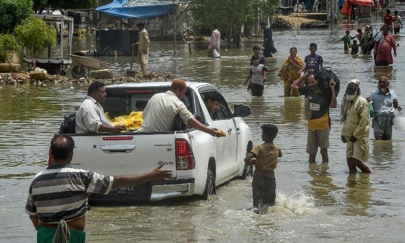 A man distributes food from a car to flood-affected people at a flooded area after heavy monsoon rains triggered floods in Karachi on August 28. — AFP