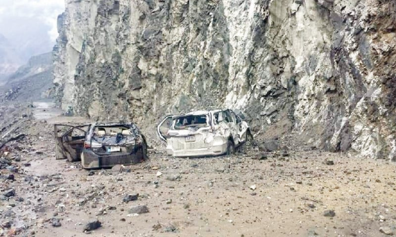 A man stands next to a house destroyed in a landslide in Upper Kohistan on Friday. (Below) A view of cars hit by landslides at Karakoram Highway near Tatta Pani in Diamer. — Dawn
