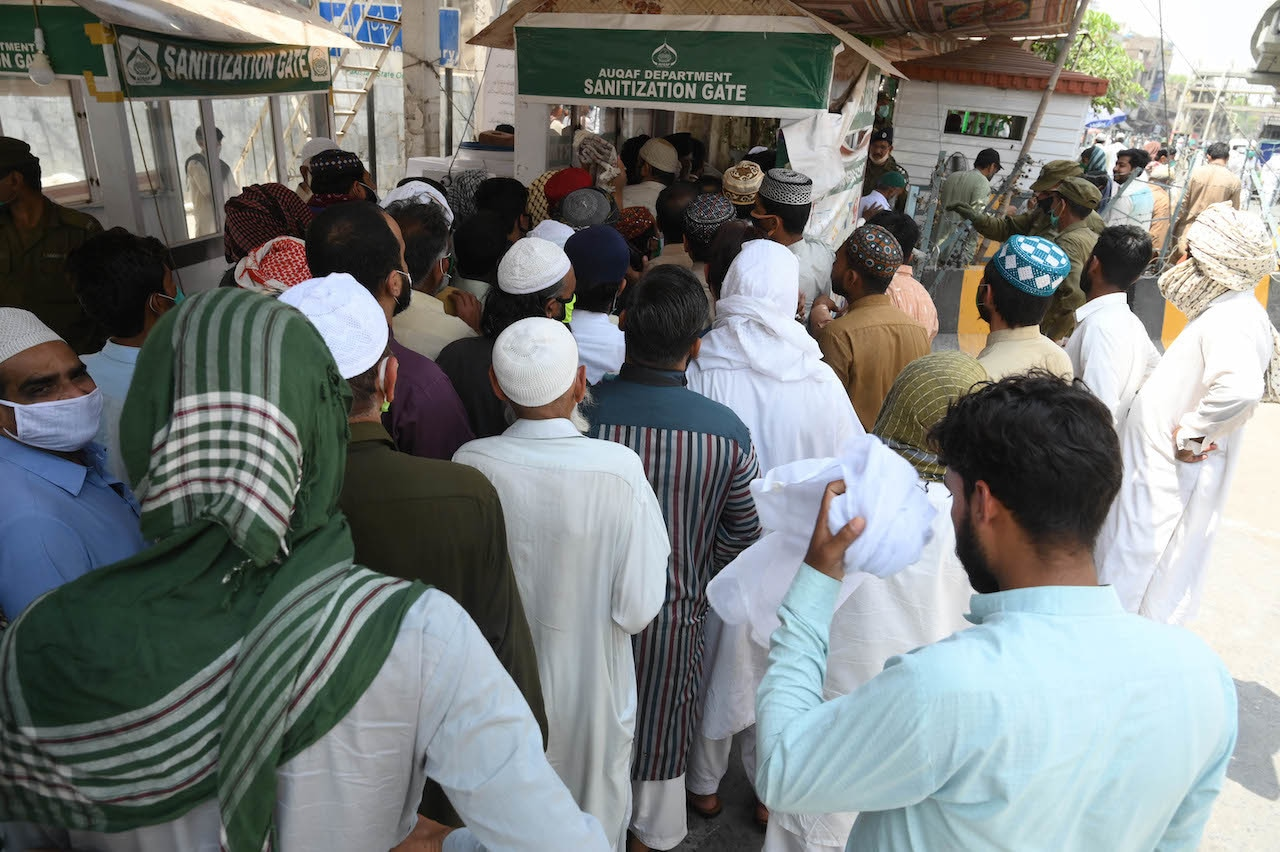 Men gather outside Data Darbar's new sanitisation gate | Arif Ali/White Star
