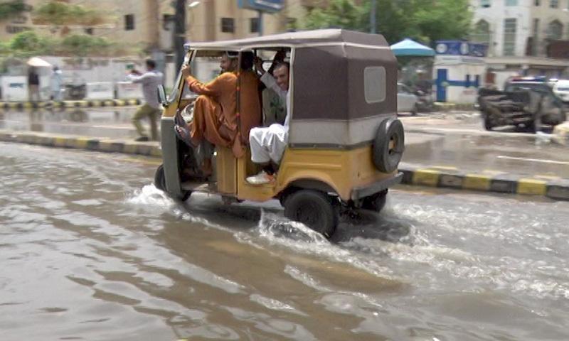A rickshaw passes on a flooded street in Karachi on Saturday. — DawnNewsTV