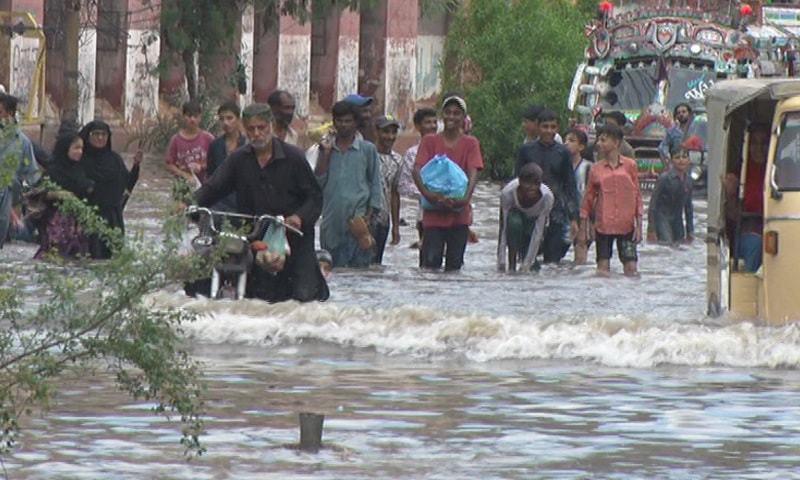People wade through a flooded road in Saddar area on Saturday. — DawnNewsTV