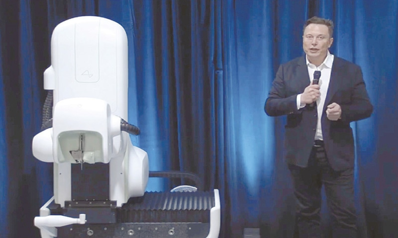 THIS video grab shows Elon Musk standing next to the surgical robot during his presentation. — AFP