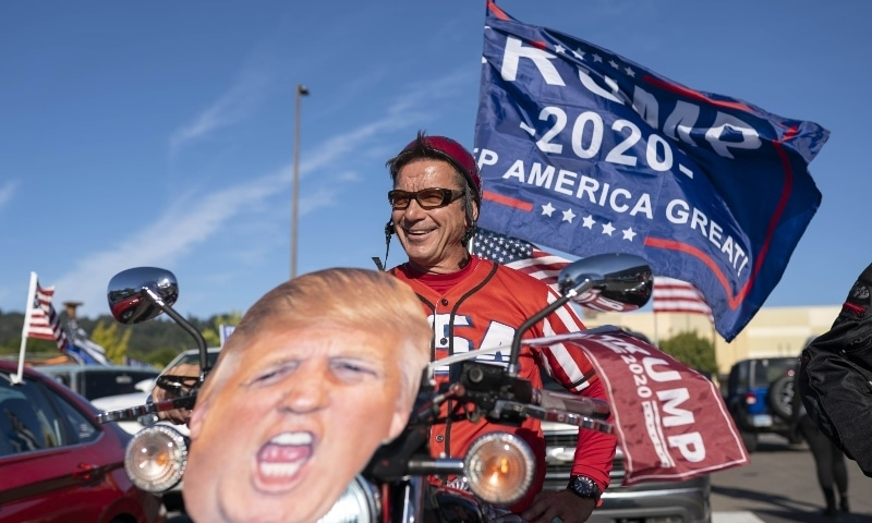 A man displays a US President Donald Trump cutout on the front of his motorcycle during a rally in support of the president on August 29 in Oregon. — AFP