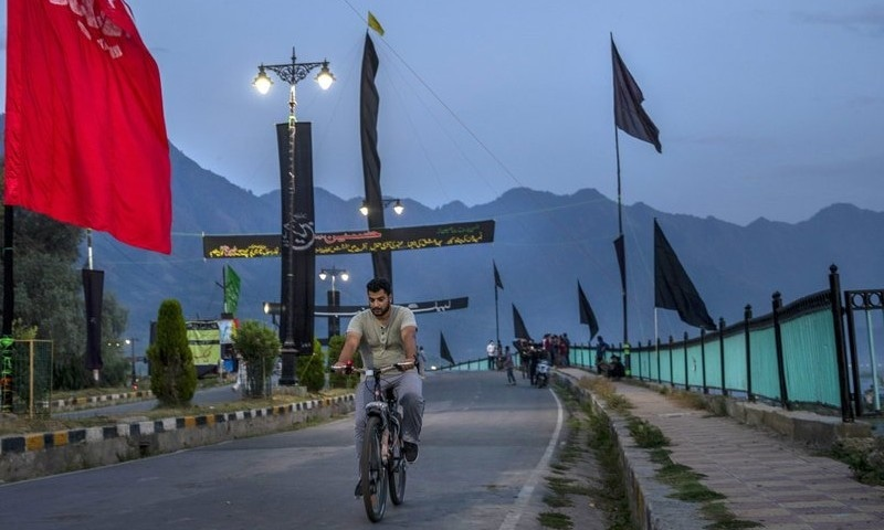 A Kashmiri man cycles past religious banners and flags erected by Shia Muslims to commemorate Muharram on a deserted street on the outskirts of Srinagar on August 25. — AP