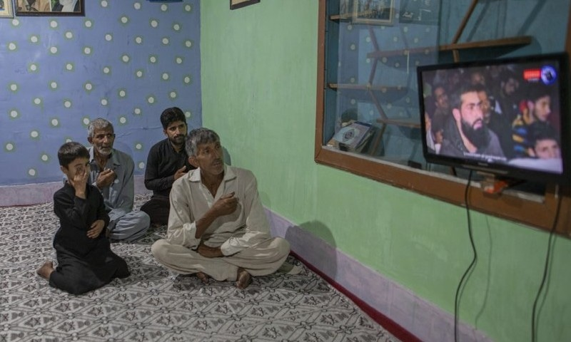 Kashmiri Shia Muslims beat their chest as they watch a religious broadcast on cable television to commemorate Muharram inside their house in the interiors of Dal Lake in Srinagar on August 24. — AP