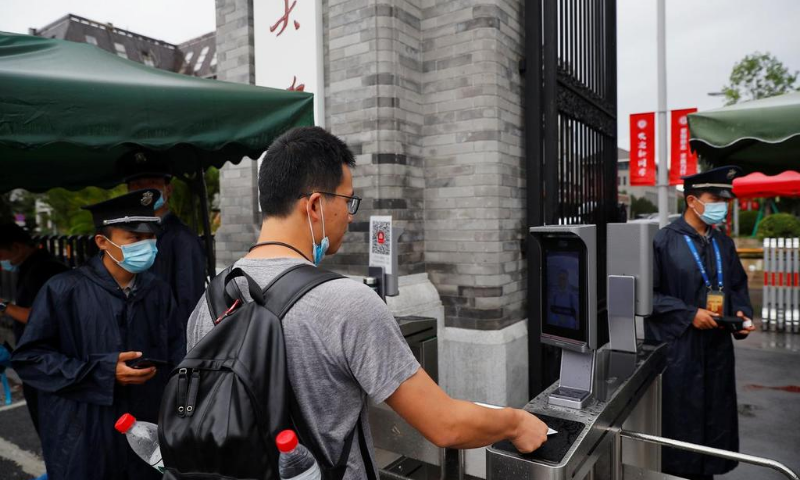 People pass facial recognition camera-controlled gates to enter Peking University as Chinese students gradually return to their campuses after an outbreak of the coronavirus in Beijing, China. — Reuters