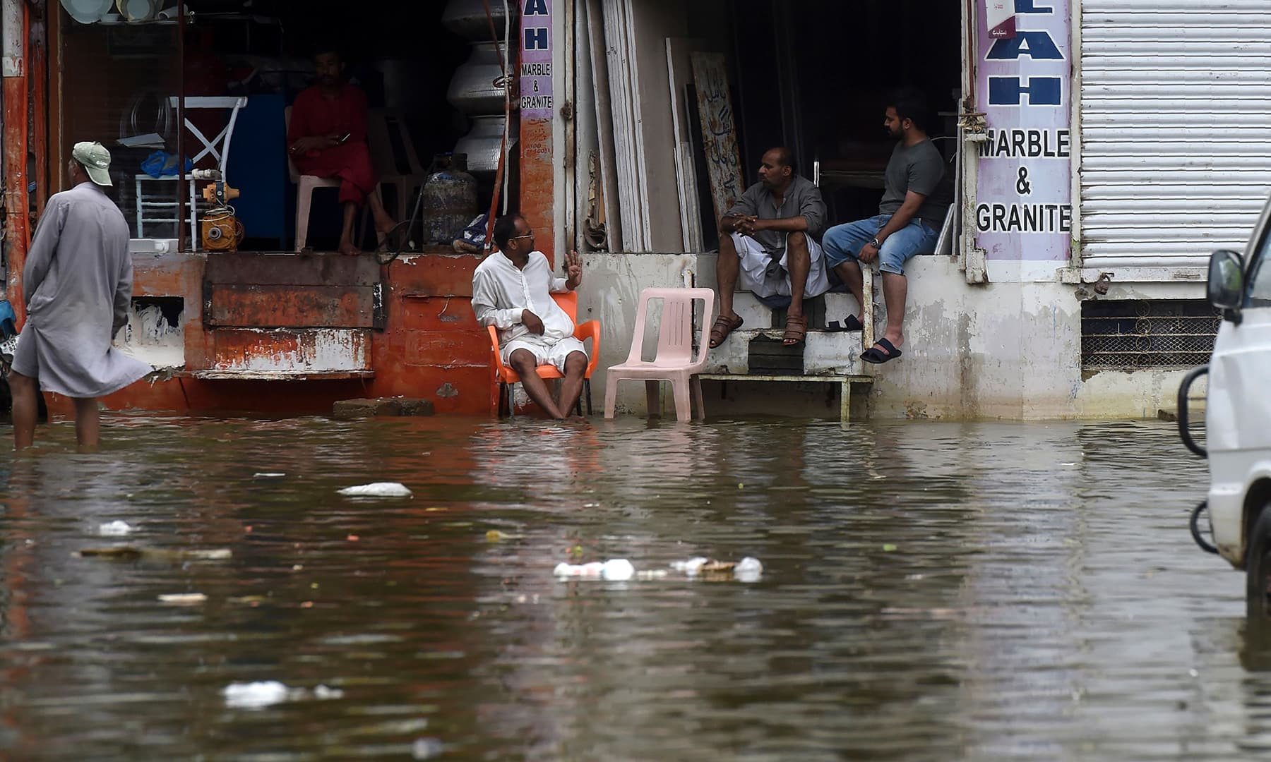 Shopkeepers sit in a flooded residential area following heavy monsoon rains in Karachi on August 31. — AFP