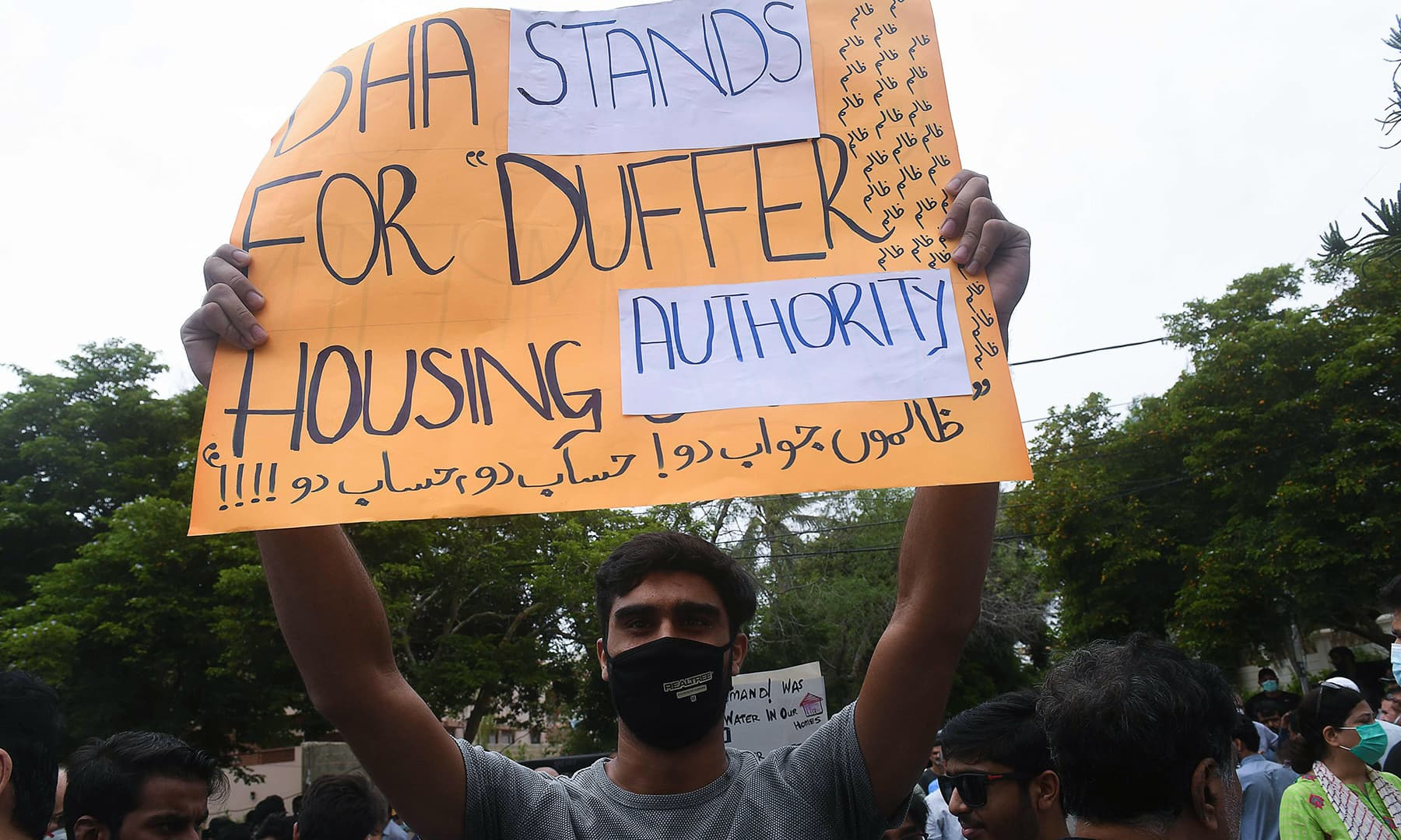 A resident of DHA holds a placard during a protest outside the CBC office on Monday. — AFP