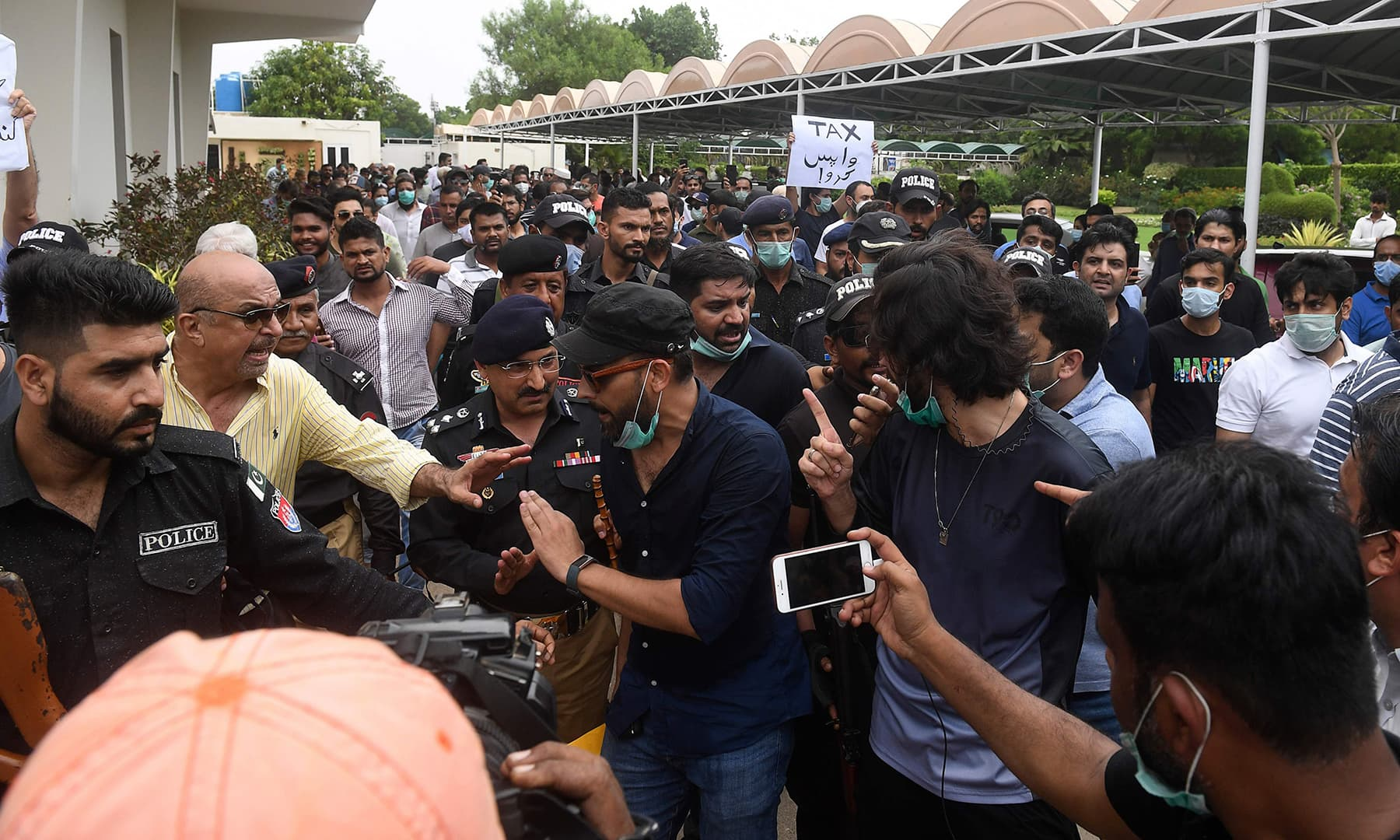 Residents of the Defence Housing Authority (DHA) gather outside the Cantonment Board Clifton (CBC) office to protest against the failure to fix drainage problems following heavy monsoon rains in Karachi on August 31. — AFP