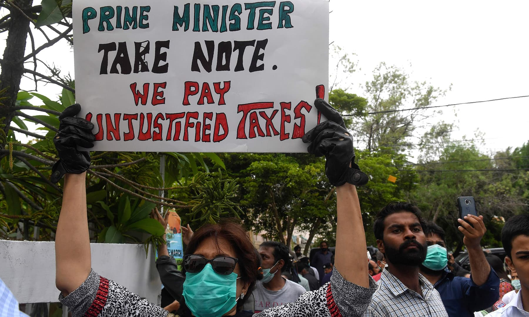 A resident of DHA holds a placard during a protest outside the CBC office in Karachi. — AFP