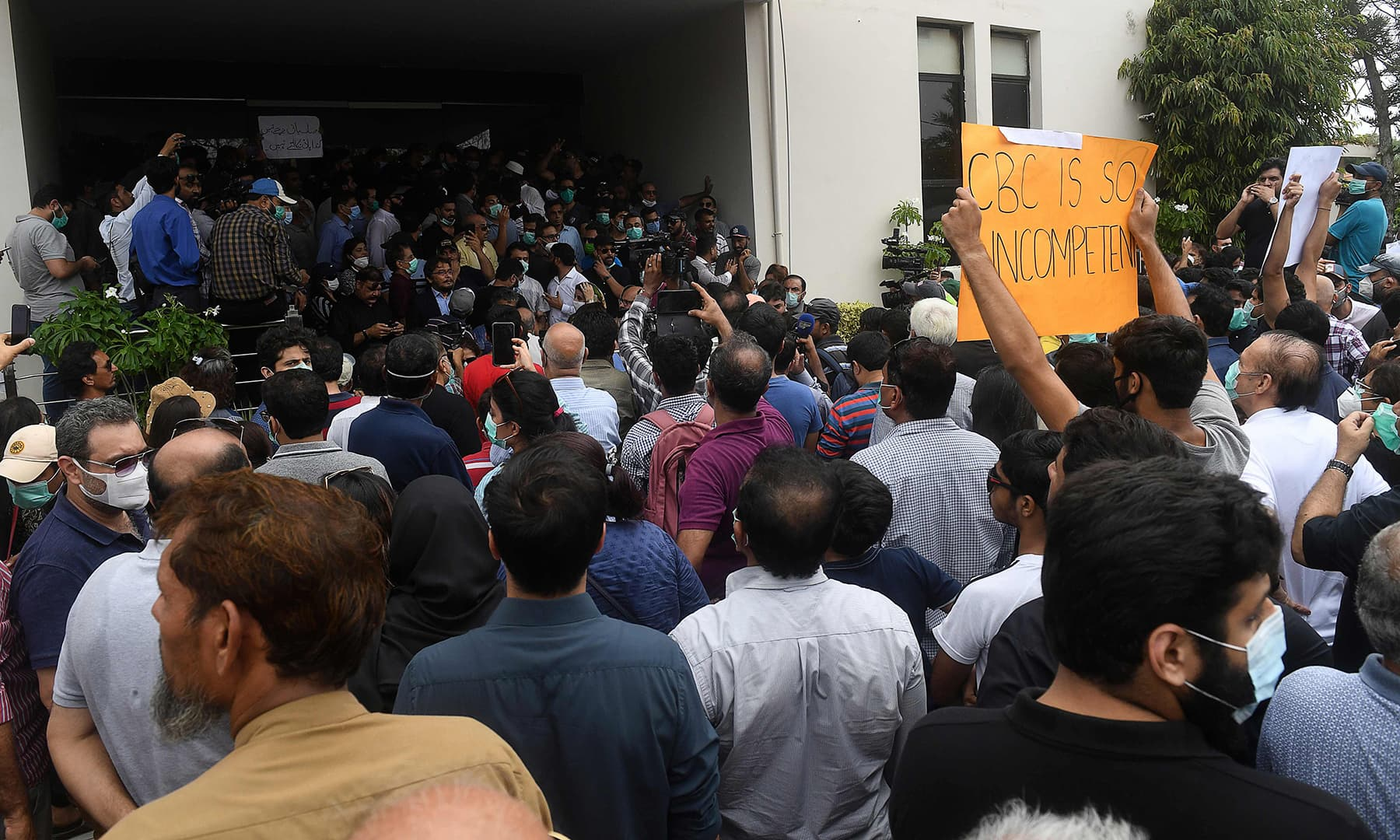 Residents of DHA hold placards as they gather outside the CBC office to protest on Monday. — AFP