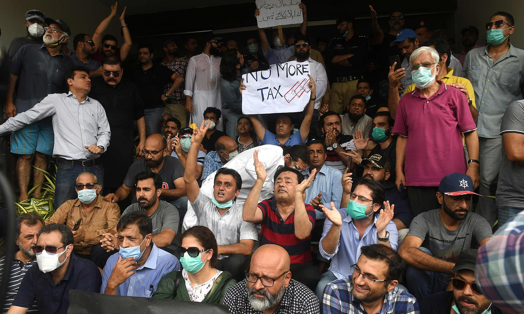 Residents of DHA chant slogans as they gather outside the CBC office to protest against the failure to fix drainage problems. — AFP