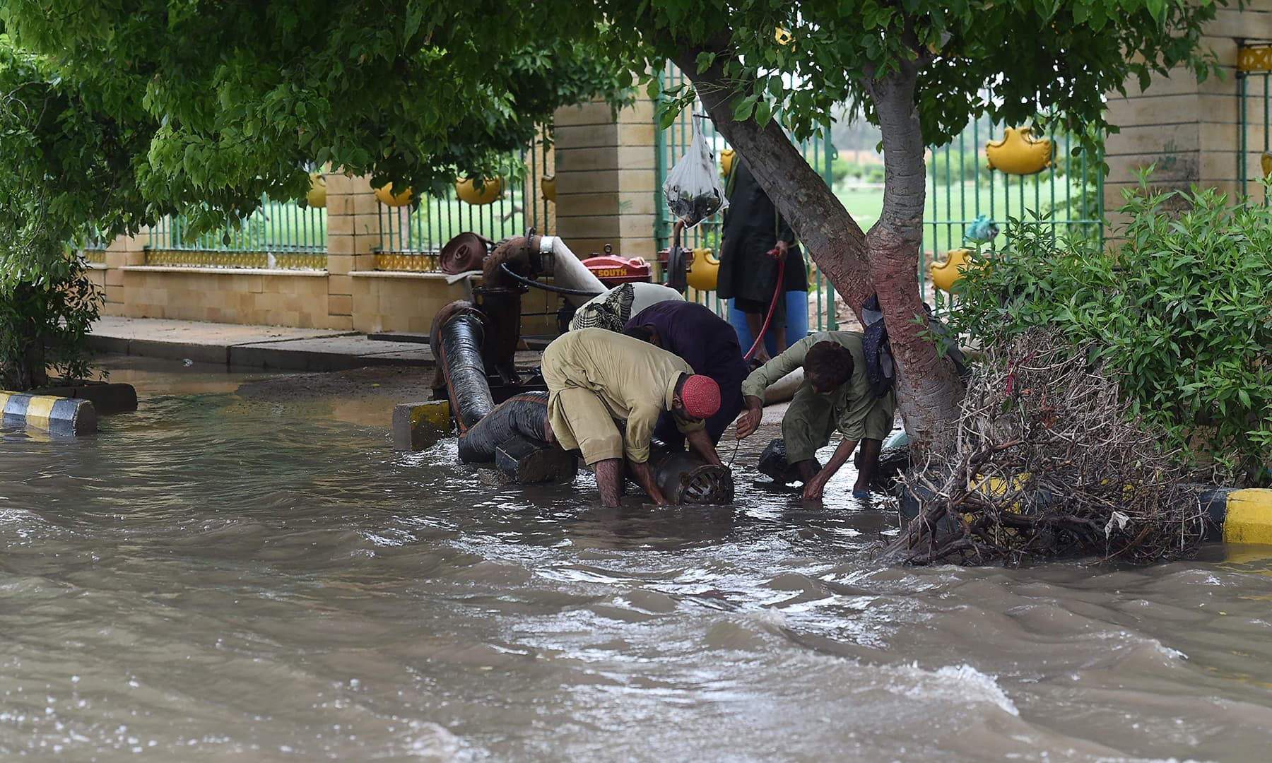 Workers use a pump to remove water from a flooded area following heavy monsoon rains in Karachi, on August 31. — AFP