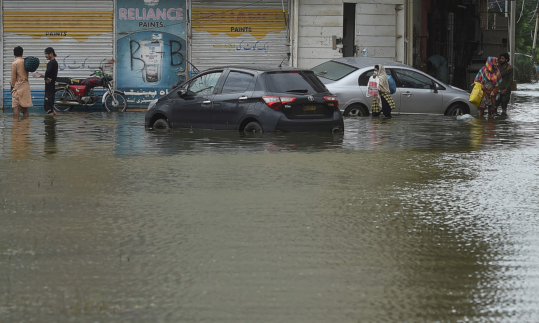 Residents wade through a flooded residential area following heavy monsoon rains in Karachi on August 31. — AFP