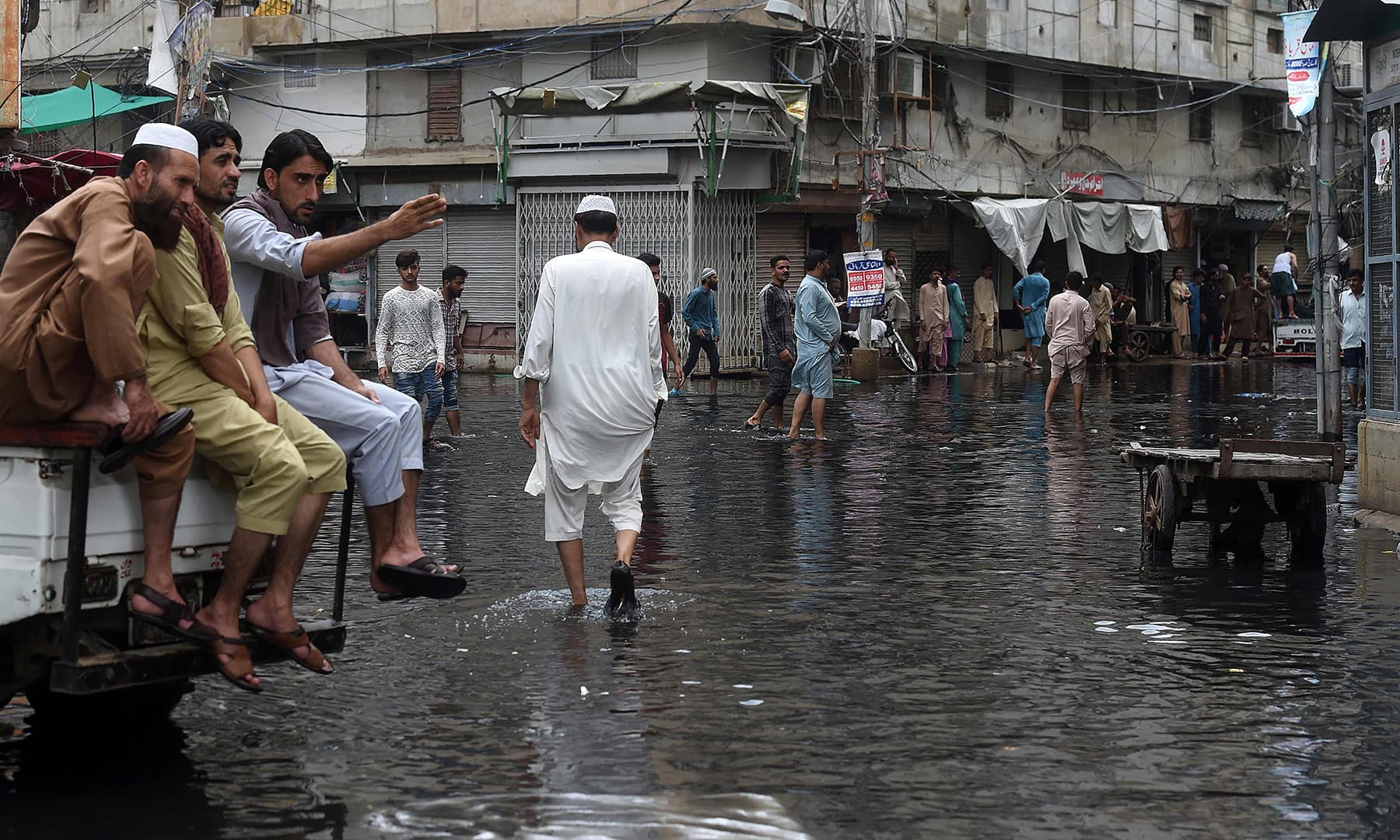 Men wade along a flooded street after heavy monsoon rains in Karachi on August 31. — AFP