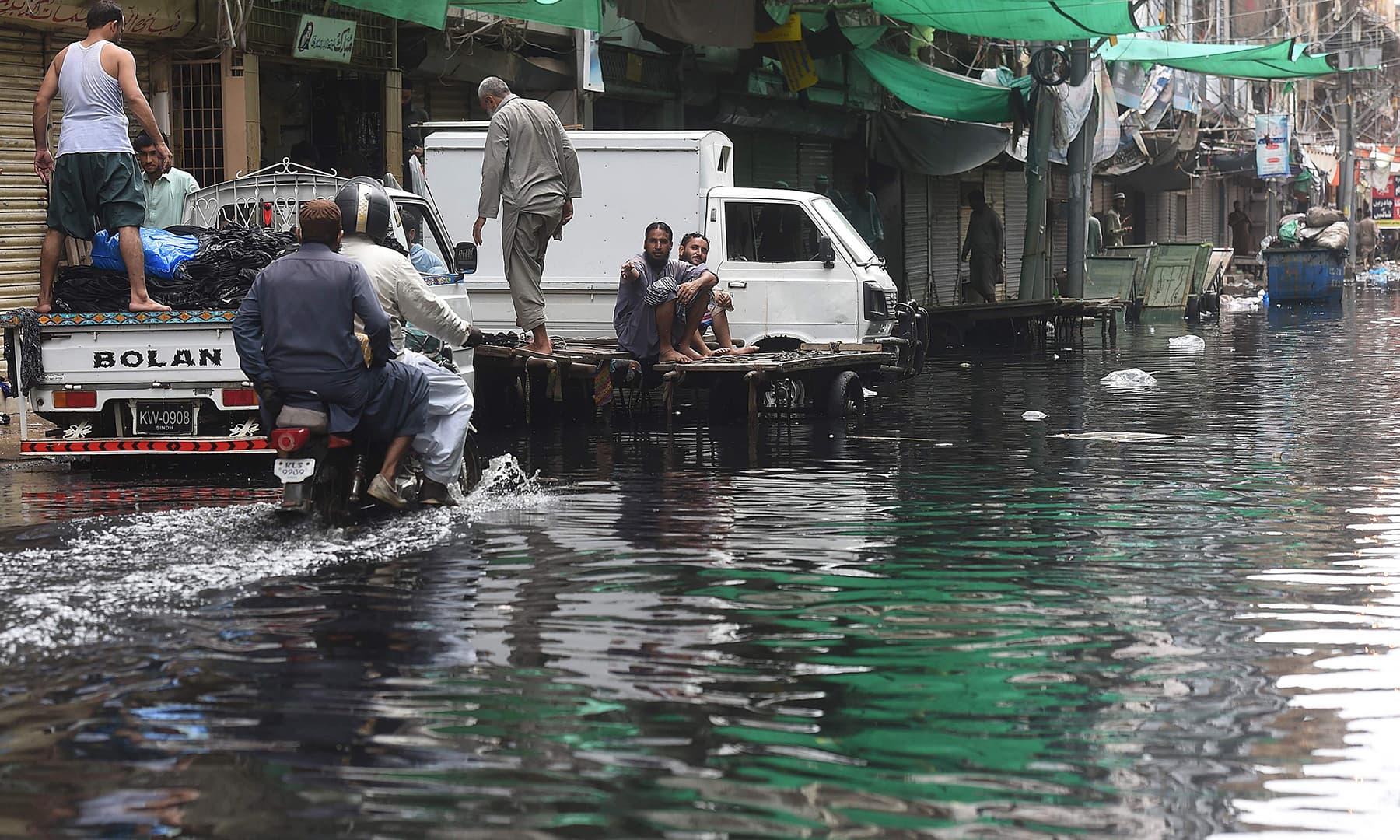 Men ride on a motorbike along a flooded street after heavy monsoon rains in Karachi on August 31. — AFP