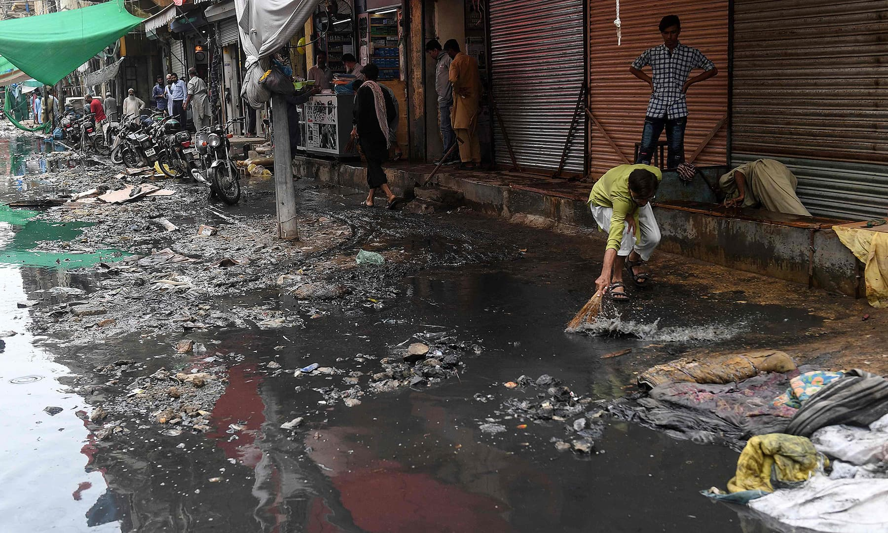 A man cleans in front of shops after a street flooded following heavy monsoon rains in Karachi on August 31. — AFP