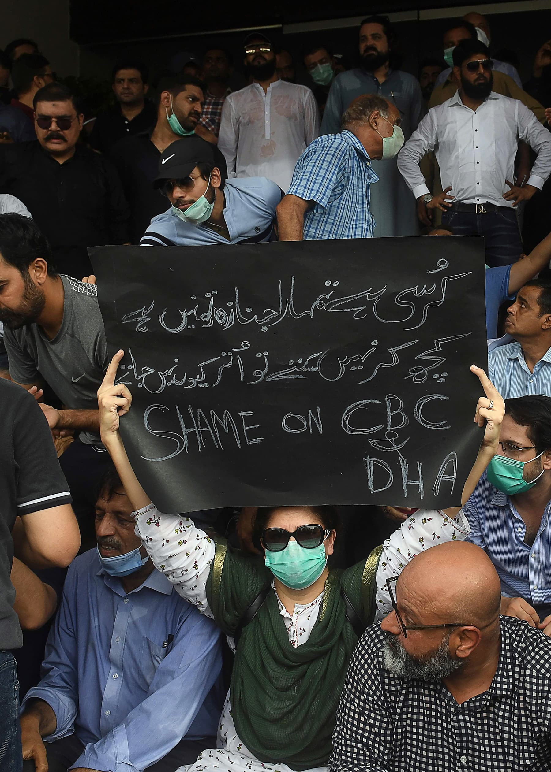 Angry residents of DHA chant slogans as they gather outside the CBC office to protest on Monday. — AFP